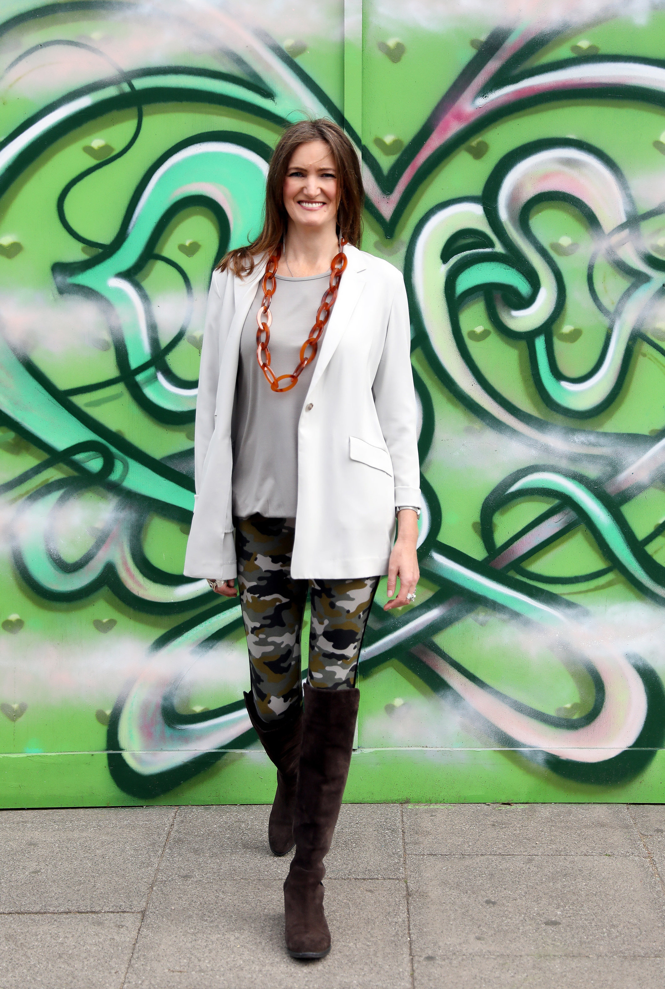 Alice Asquith wears Asquith camouflage yoga leggings against a graffiti wall.