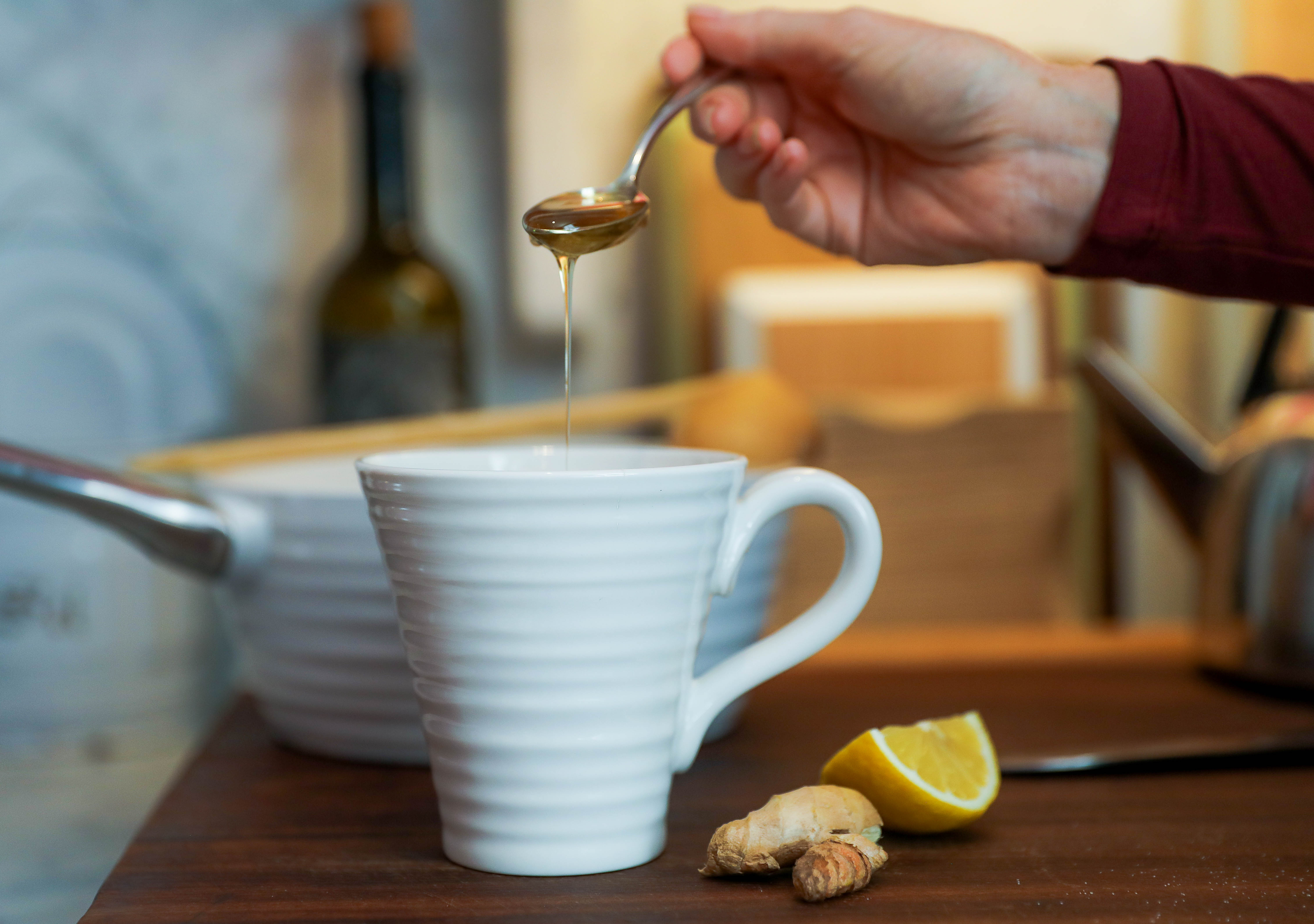 Sophie Conran pouring honey into her ceramic collection in an Asquith jumpsuit.